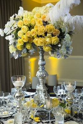 Silver stand with yellow flowers, silver leaves, and white feathers