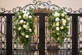 black gate with white flowers and greenery to serve as backdrop of ceremony