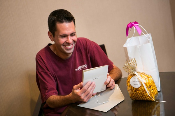 a smiling groom reads letter from his bride accompanied by a gift