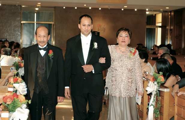 Groom with father and mother walk down aisle