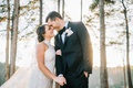 bride in high neck lace wedding dress groom in suit and bow tie foreheads touching winter portrait