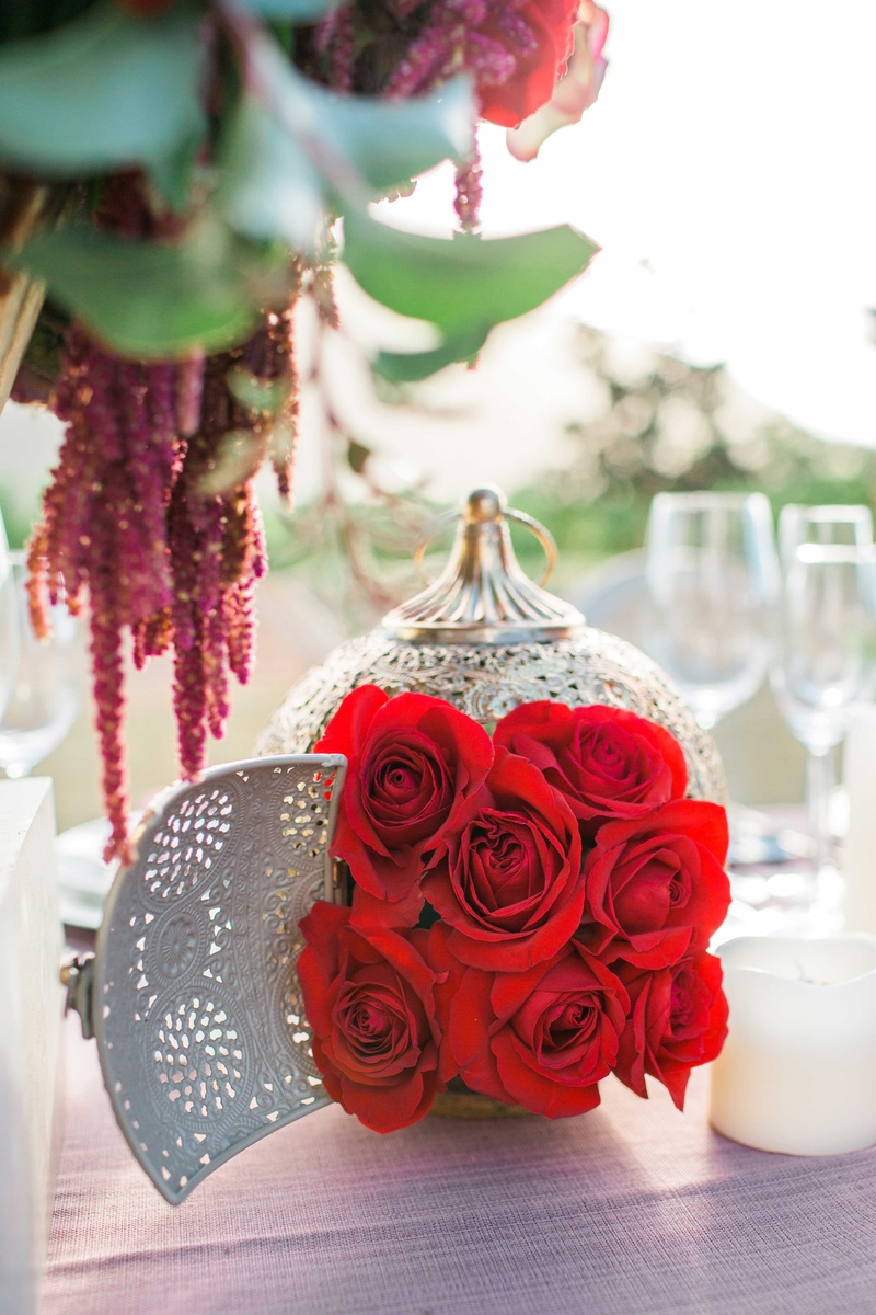 red rose bouquet in gold lantern on pink table linen in rustic vineyard setting