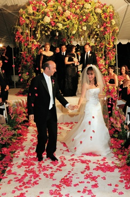 Bride and groom in front of flower chuppah at nighttime wedding ceremony