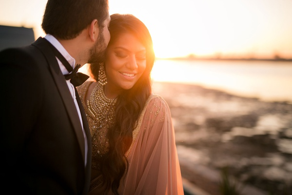 bride and groom at sunset in lehnga and tuxedo for dinner with friends and family