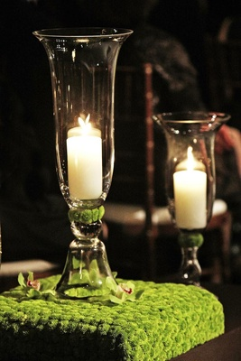Candle in glass vase on top of green flower stand