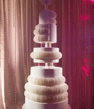White wedding cake fan design contemporary motif hanging from chuppah acrylic crystal strands