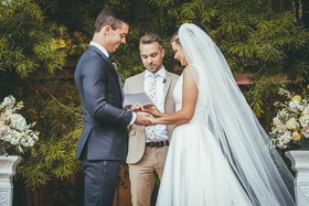 bride in stella york wedding dress, groom in navy suit, officiant in khaki suit