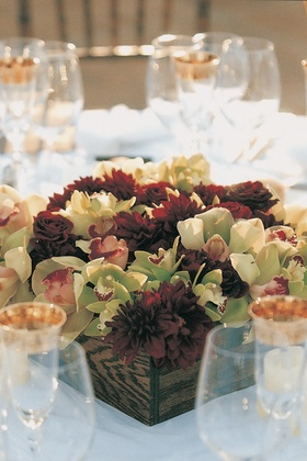 Red and green flowers in wood centerpieces