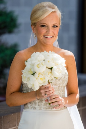 Blonde woman with updo holds ivory flowers