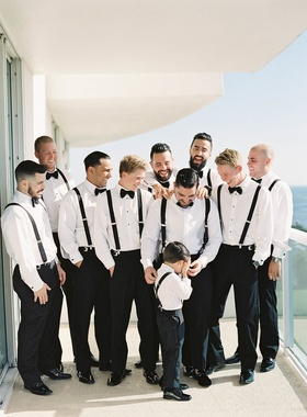 Groom and groomsmen on balcony with ring bearer all in tuxedo pants suspenders and bow ties