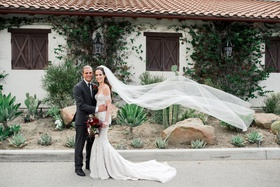 groom in manbun and charcoal suit, bride in pallas couture wedding dress, flowing cathedral veil