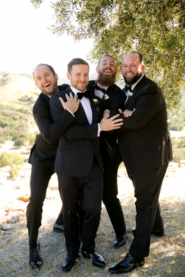 funny groomsmen picture, groom and groomsmen in tuxedos playfully pose