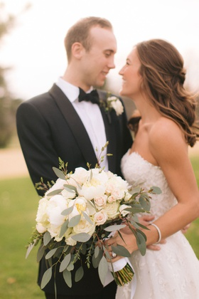 groom in tuxedo bow tie bride in strapless reem acra wedding dress ivory bouquet half up half down