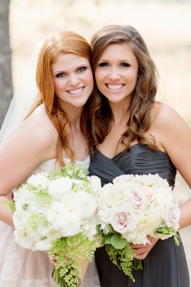 Bride in lace blush dress with bridesmaid and sister in charcoal gown