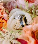 bridal bouquet white pink orange flowers round solitaire engagement ring men's band black gold