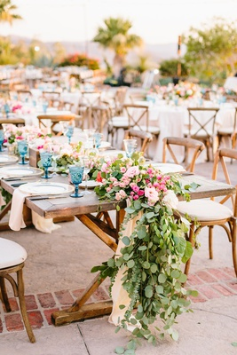 outdoor wedding reception wood table wood vineyard chairs blue colored goblet greenery pink flowers