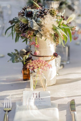 wildflower and pinecone centerpieces wrapped on book pages tied in twine.