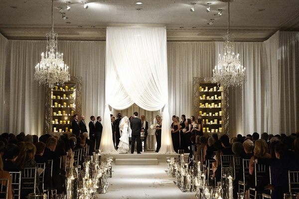 Bride and groom married beneath white chuppah