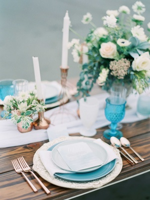 blue white green and rose gold tablescape on top of a wooden table with low lush floral arrangement
