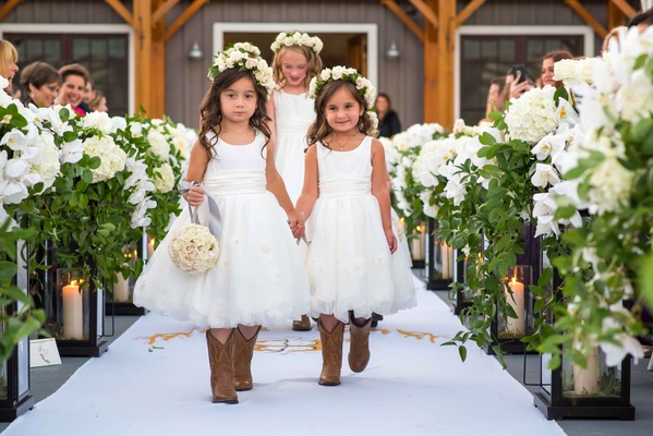 Flower girls holding hands walking down aisle flower crown cowboy boots pomander ball of flowers