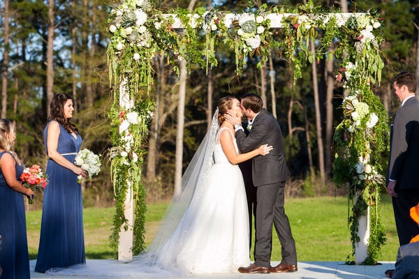 Bride and groom first kiss at outdoor rustic wedding ceremony with white arch and greenery