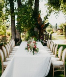 wedding reception inspiration long table low centerpiece garden style wood upholstery chairs trees