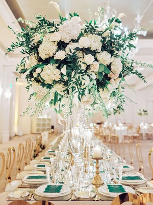 wedding reception long table modern gold chairs white greenery centerpiece green menu gold candles