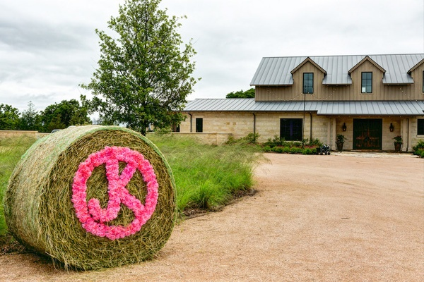 Roll of hay with initials in pink flowers outside ranch