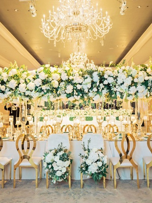 wedding reception head table fur bride groom chairs gold seating tall centerpiece overhead crystals