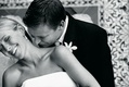 Black and white photo of groom kissing bride's neck