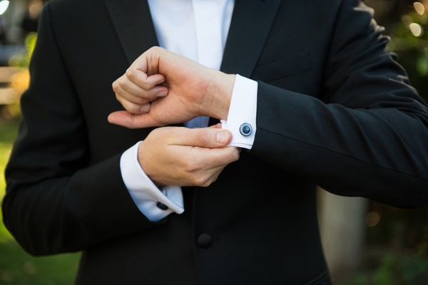 groom in classic black tuxedo shows round cuff links