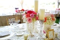Wedding reception table with pink and white flowers in beaded vases and pillar candles