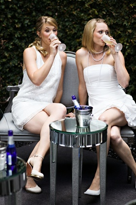 Guests in white dresses drink Champagne