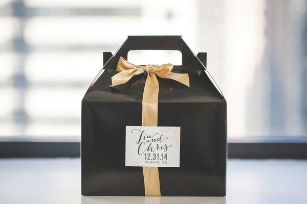 Black favor box with gold ribbon and white label for New Year's Eve wedding guests