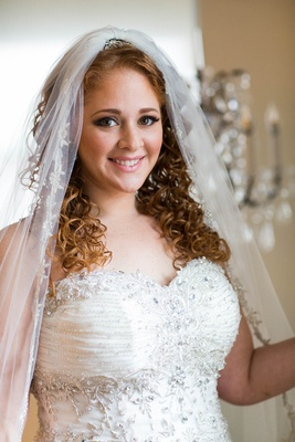 Bride in sweetheart neckline wedding dress with curly red hair and embroidered veil