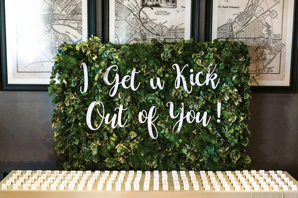 "escort card table with small greenery wall behind with ""I get a kick out of you"" in laser-cut letter"