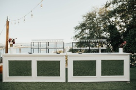 outdoor wedding reception cocktail hour white mirror hedge bar greenery shelving string bistro light