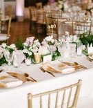 Gold charger plate, low centerpieces greenery pink flowers calligraphy table number gold chairs