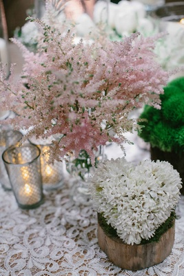 Wood stump with white flower heart shape centerpiece pink soft flowers on lace table linen