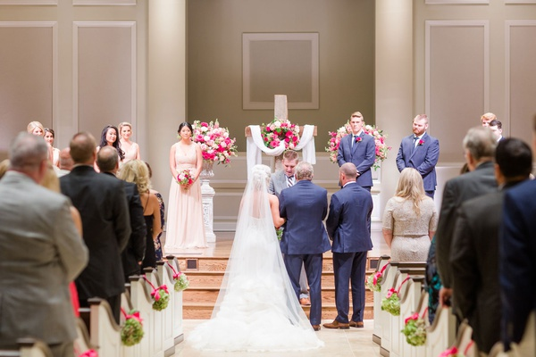 wedding ceremony church cross at altar white pink flowers guests pews decorated with green pink deco