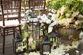 lanterns with candles set at flower petals behind chiavari chairs