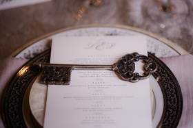 Wedding reception place setting with gold rimmed plate, pearl plate, brass antique key wedding favor