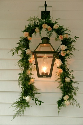 Lanterns on wall with garland of flowers