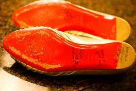 red soled shoes with signatures from loved ones
