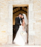 Young bride in Monique Lhuillier wedding dress and groom in suit at chapel in Texas
