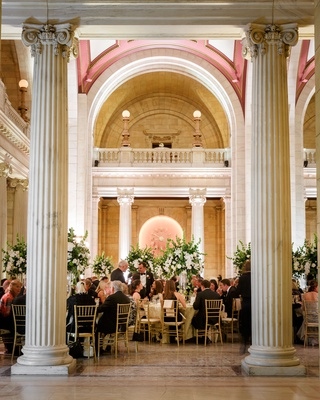 wedding reception dinner hall tall columns gold chairs white green centerpiece designs decor