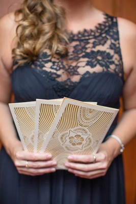Woman in navy blue lace dress holding gold and white ceremony programs