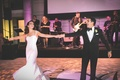 Bride and groom dancing on illuminated dance floor