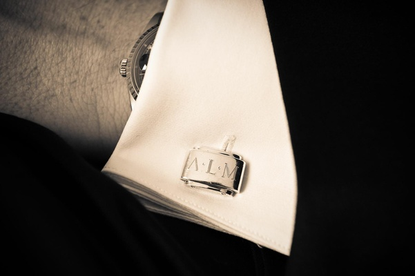 Black and white photo of cuff link with groom initials