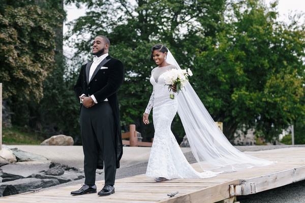 bride in long sleeve wedding dress cathedral veil updo walking toward groom long tail tux first look